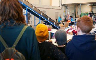 Barns som tittar på när textilsorterare arbetar